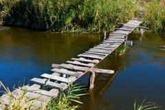 Träbro på floden Royaltyfri Bild