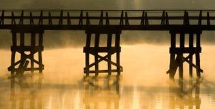 Träbro på gryning Arkivfoton