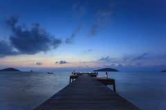 Träbro till havet i aftontid Royaltyfri Foto