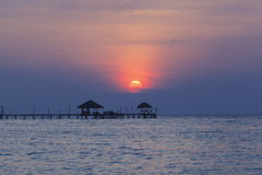 Träbro till havet i aftontid Arkivfoto