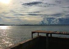 Träbro till havssikten under molnig himmel och solsken arkivfoton