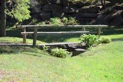 Träbro utanför över en bäck arkivbilder