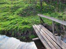 Träbro, vatten och gräs royaltyfri foto