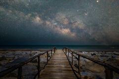Träbrogångbana till stranden med galaxen för mjölkaktig väg Royaltyfria Foton
