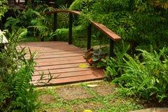 Träbron över dammet med blommaträdgården royaltyfri fotografi
