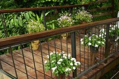 Träbron över dammet med blommaträdgården arkivbild