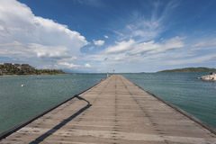 Träbron över havet och den blåa himlen arkivbilder