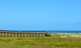 Träbron går till havstranden Royaltyfri Fotografi