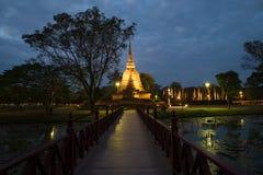 Träbron som för till, fördärvar av den forntida buddistiska templet av Wat Sa Si i aftonskymning Sukhothai Thailand arkivbilder