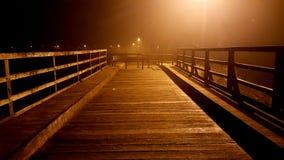 Träbrotillträde som blockeras med massiva ledstänger på den dimmiga natten Arkivbild