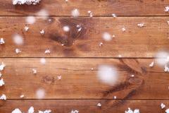 Träbrun bakgrundstabell med vita snöflingor, det tomma tomma wood brädet och fallande snö, bästa sikt, kopieringsutrymme Arkivbilder