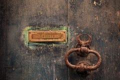 Träbrun dörrbakgrund med den rostiga bokstavsasken och det rostiga handtaget Åldrig stängd port, övre sikt för slut med detaljer Fotografering för Bildbyråer