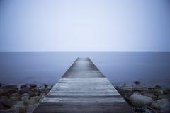 Träbrygga med blått vatten Royaltyfria Bilder