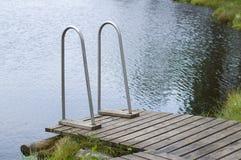 Träbrygga med trappa till dammet Arkivbilder