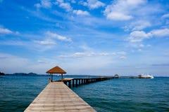 Träbrygga på över den härliga stranden med blått Arkivbild