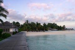 Träbrygga på en vit sandstrand med palmträd och en trevlig solnedgång med en himmel med moln royaltyfri foto