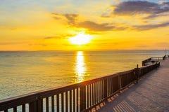 Träbrygga på stranden på solnedgången Arkivbild