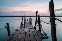 Träbrygga ut till havet under solnedgång royaltyfri fotografi
