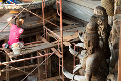 Träbuddistiska statyer med repairmanen i bakgrund på återställandeplatsen på sidoyttersidan av fristaden av sanning, Thailand royaltyfri fotografi