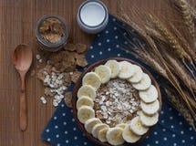 Träbunke av den organiska cornflakes och havremjölet med bananen Näringsrik frukost, råkostingredienser Royaltyfri Fotografi