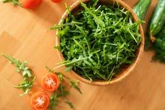 Träbunke av ny gräsplan, naturlig arugula med körsbärsröda tomater och gurkor Royaltyfri Bild