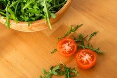 Träbunke av ny gräsplan, naturlig arugula med körsbärsröda tomater på en trätabell Arkivbild