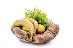 Träbunke med äpplen, bananer och druvor Royaltyfria Foton