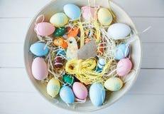 Träbunke med gula, rosa och gröna ägg för apelsin, på vit träbakgrund Lycklig påsk! Garnering royaltyfri foto