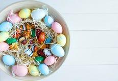 Träbunke med gula, rosa och gröna ägg för apelsin, på vit träbakgrund Lycklig påsk! Garnering royaltyfri bild