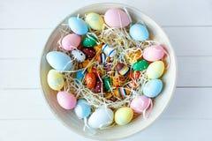 Träbunke med gula, rosa och gröna ägg för apelsin, på vit träbakgrund Lycklig påsk! Garnering royaltyfria bilder