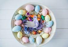 Träbunke med gula, rosa och gröna ägg för apelsin, på vit träbakgrund Lycklig påsk! Garnering arkivbilder