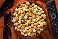 Träbunke med sött popcorn, TVfjärrkontroll och exponeringsglas 3D på orange sängkläder Top beskådar Mellanmål och mat för en film Royaltyfria Foton