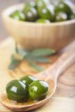 Träbunke och sked med gröna oliv och olivolja Royaltyfri Fotografi