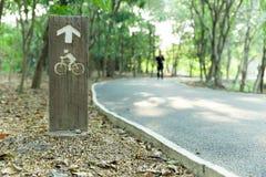 Träcykelvägmärke i parkera Arkivbild