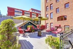Trädäck med röda stolar och grillfesten Bostads- byggnad I Arkivbild