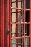 Trädörr av en gammal röd telefonask Arkivfoto