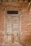 Trädörr för gammal tappning på väggen för röd tegelsten Arkivfoto