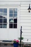 Trädörr för vit tappning mot den vita väggen och en lampa Arkivfoton