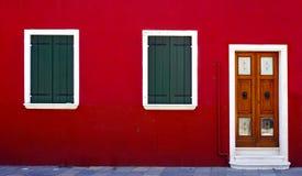 Trädörr och två fönster på den röda väggen royaltyfri fotografi