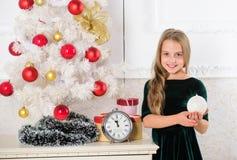 Träd för ungeflickajul som väntar den midnatta klockan Barndomlyckabegrepp Barnet firar jul hemma favorit royaltyfria foton