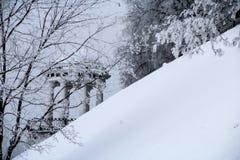 Träd med filialer som täckas av frost och gazeboen Arkivbild