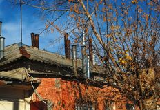Träd med kala filialer på bakgrunden av ett gammalt historiskt hus med röda väggar och många lampglas på taket Royaltyfria Bilder