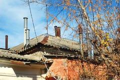 Träd med kala filialer på bakgrunden av ett gammalt historiskt hus med röda väggar och många lampglas på taket Royaltyfri Foto