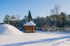 Träd och hus i vinter, en gazebo i snön Arkivbilder
