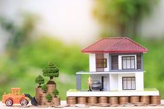 Träd som växer på mynt pengar och lastbil, leker med miniatyraffärsmananseende på modellhus och bilen på naturlig gräsplan royaltyfri fotografi