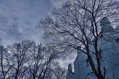 Träd utan sidor på bakgrunden av ett gammalt dystert hus och moln i aftonhimlen, sorgsenhet Arkivbilder