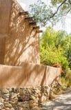 Trädet gjuter skuggor på Adobeväggen på Canyon Road i Santa Fe som är ny Royaltyfria Bilder
