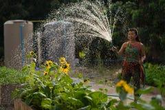 Trädgård för hem för kvinnasprejvatten Arkivbild