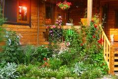 Trädgård med blomsterrabatt- och husfarstubron Royaltyfri Fotografi