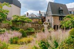 Trädgård med byststatyn och medeltida arkitektur i centret av Rouen, Frankrike royaltyfri bild